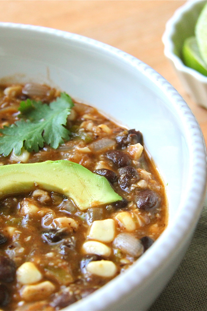 Black bean soup with corn, tomatillos, and topped with slices of avocado.