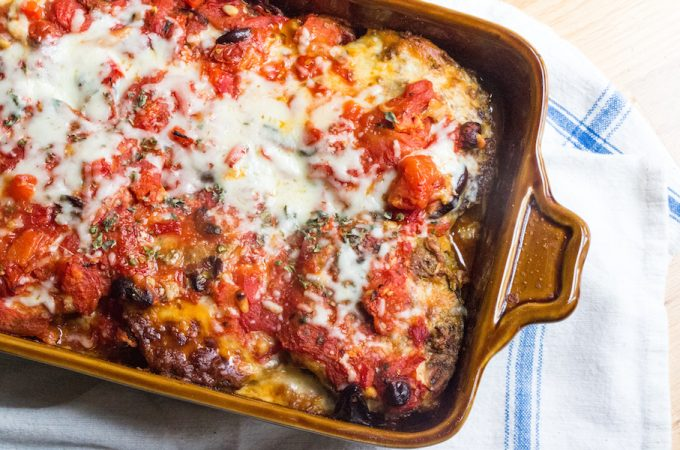 Recipe for slices of eggplant dipped in pesto and parmesan cheese, layered in a casserole with roasted tomato sauce and mozarella.