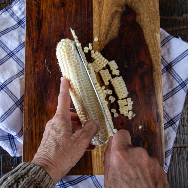 Slicing corn from a cob with chef's knife